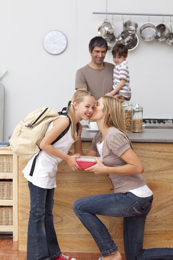 Mère donnant à son descendant le repas scolaire image libre de droits
