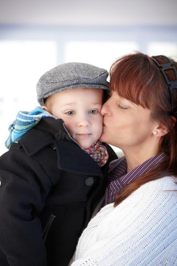 Mère embrassant l'enfant en bas âge mignon photo stock