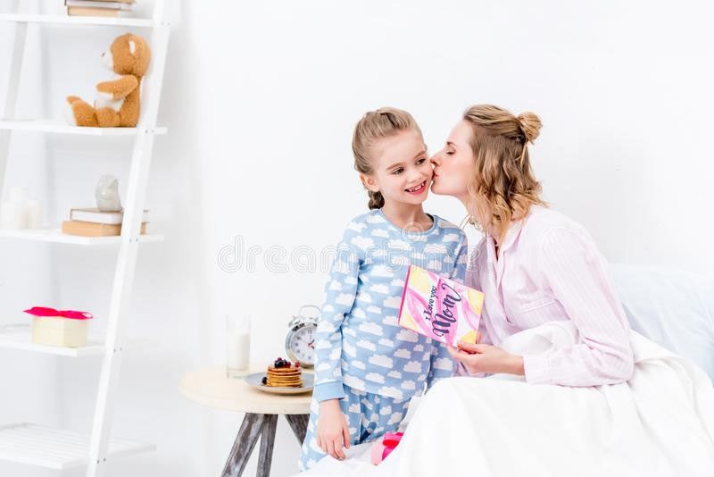 mère embrassant la fille pour des présents sur heureux photo libre de droits