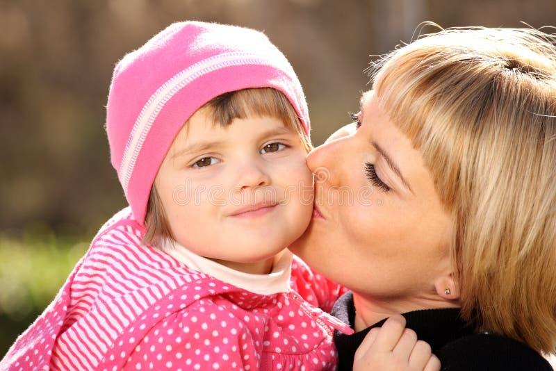 Mère embrassant sa petite fille image stock