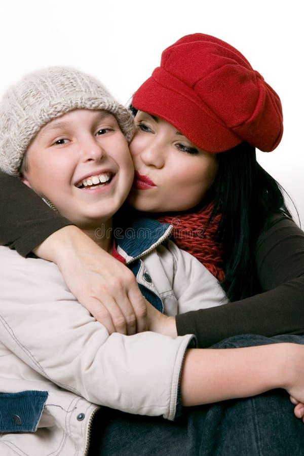 Mère embrassant son enfant sur la joue. image stock