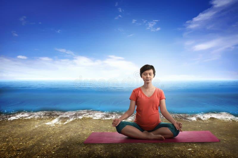 Mère enceinte d'Asiatique faisant le yoga images stock