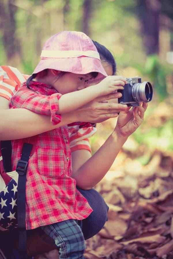 Mère enseignant la belle fille asiatique prenant des photos outdoors photographie stock libre de droits