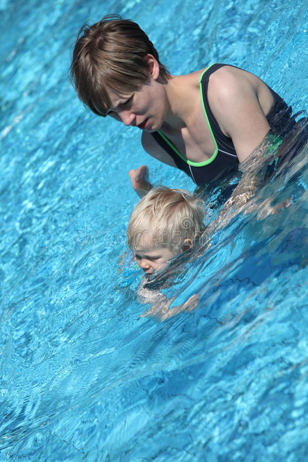 Mère enseignant son petit descendant à nager photo libre de droits