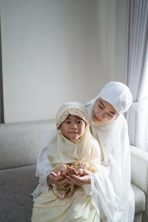 Mère enseigner sa fille à prier image stock