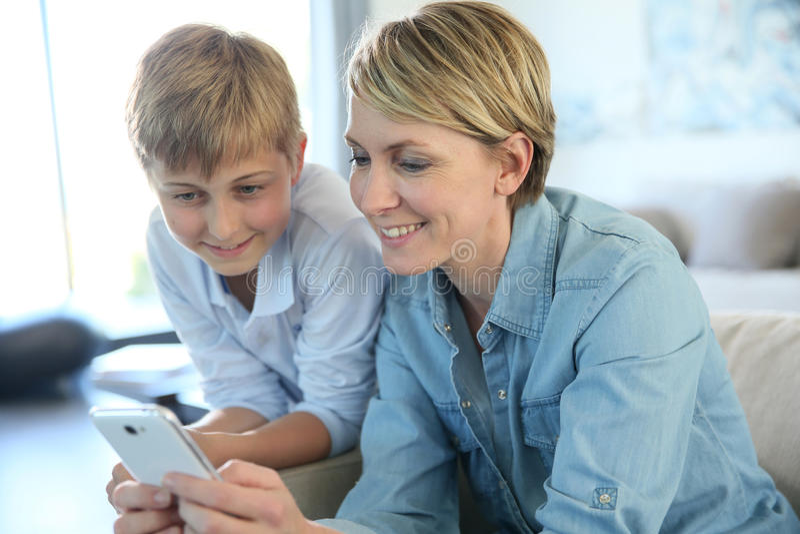 Mère et adolescent bientôt utilisant le smartphone images libres de droits