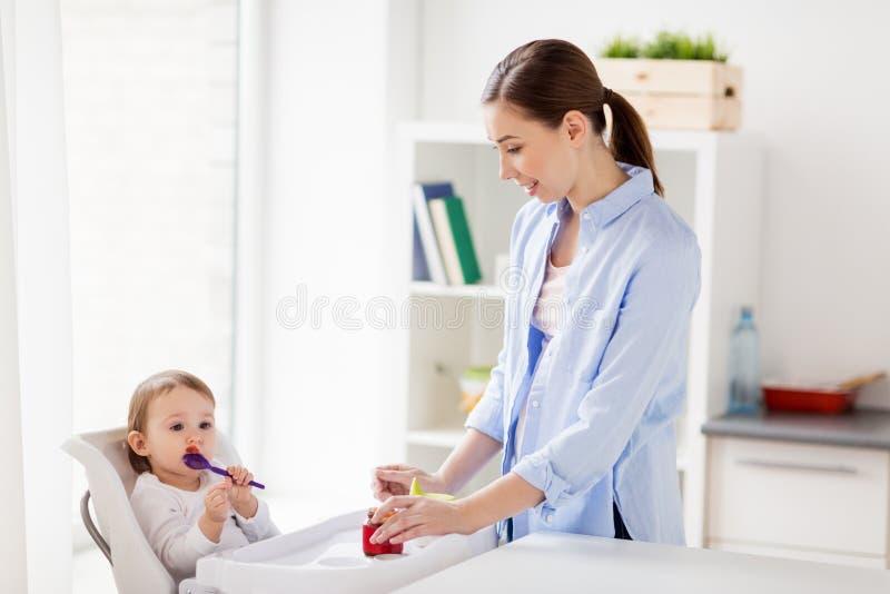 Mère et bébé avec la cuillère mangeant de la purée à la maison photographie stock libre de droits