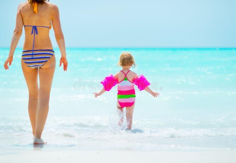 Mère et bébé entrant dans la mer blanc d'isolement de vue arrière image stock
