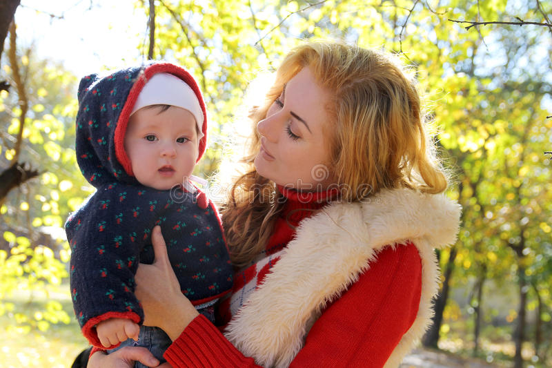 Mère et bébé parlant en parc d'automne image libre de droits