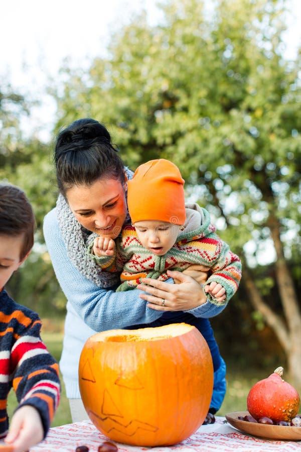 Mère et bébé regardant dans le potiron de Halloween photos libres de droits