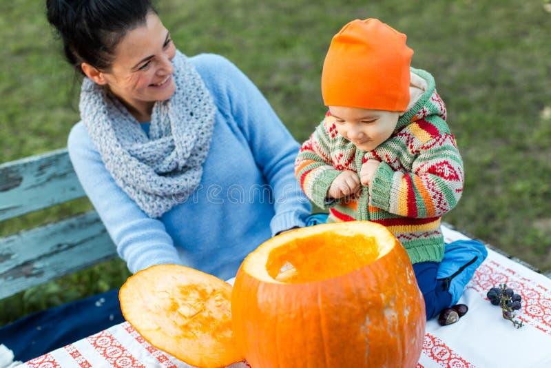 Mère et bébé regardant dans le potiron ouvert de Halloween photo libre de droits