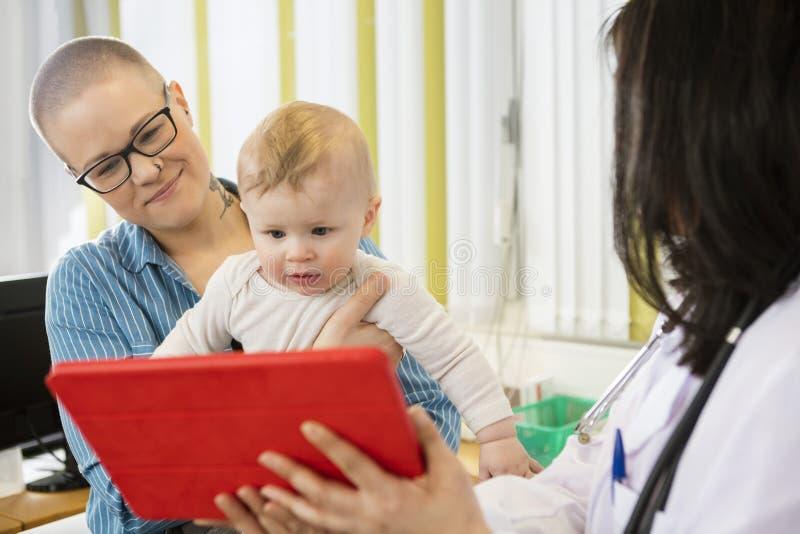 Mère et bébé regardant la Tablette de Digital tenue par le docteur image stock