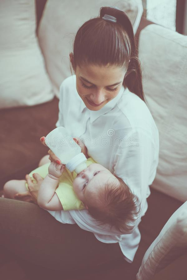 Mère et bébé souriants à la maison image stock