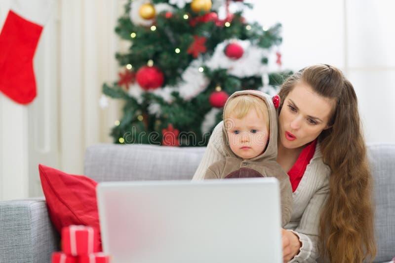 Mère et chéri près d'arbre de Noël utilisant l'ordinateur portatif photos libres de droits