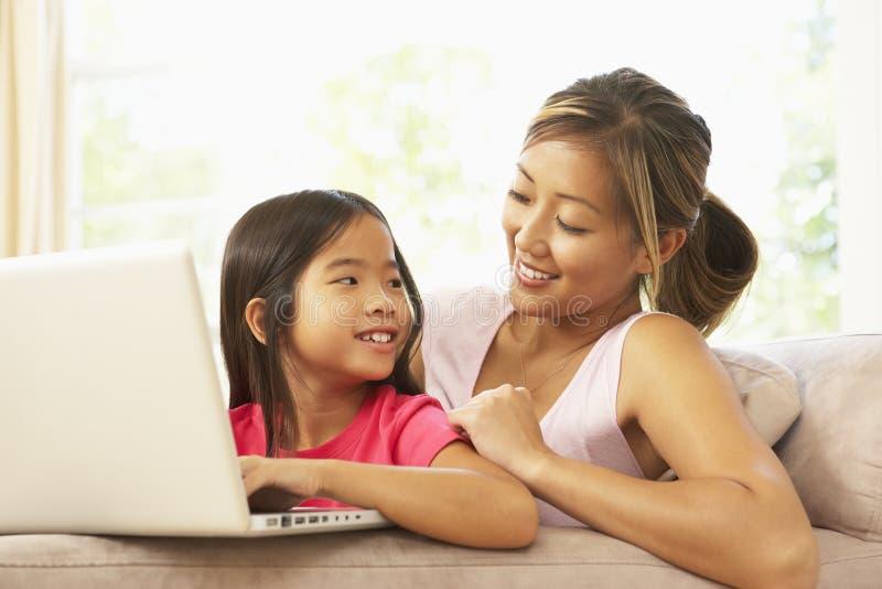 Mère et descendant à l'aide de l'ordinateur portatif à la maison photo libre de droits