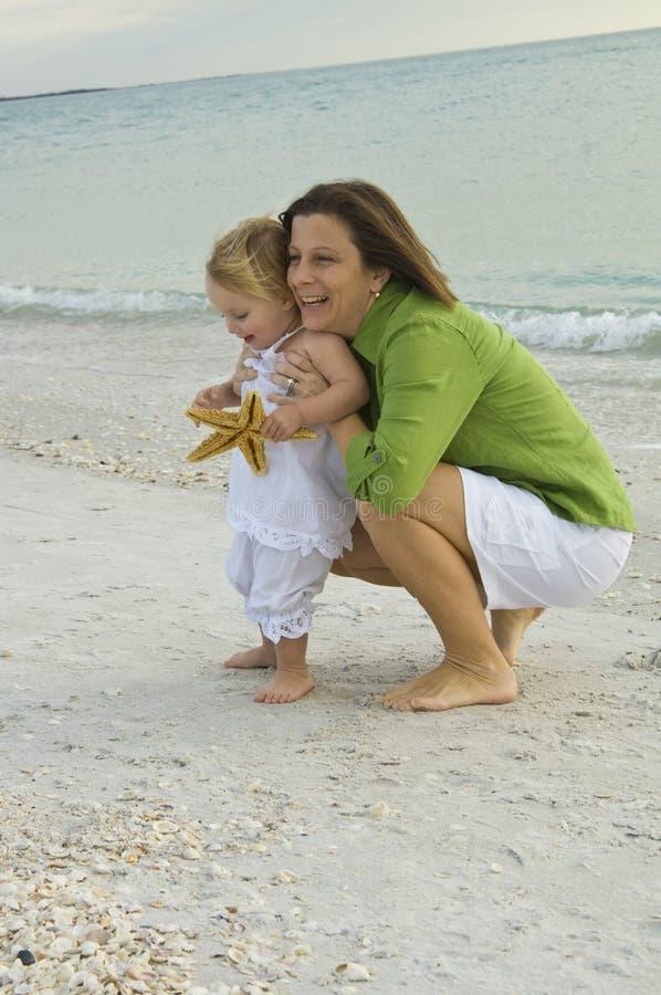 Mère et descendant à la plage photo stock