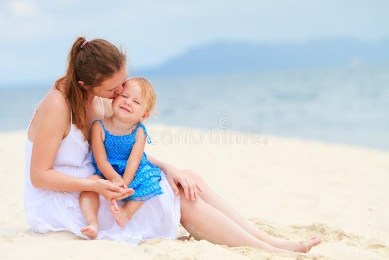 Mère et descendant affectueux sur la plage tropicale photographie stock