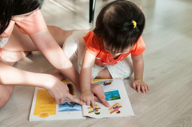 Mère et descendant affichant un livre ensemble image stock