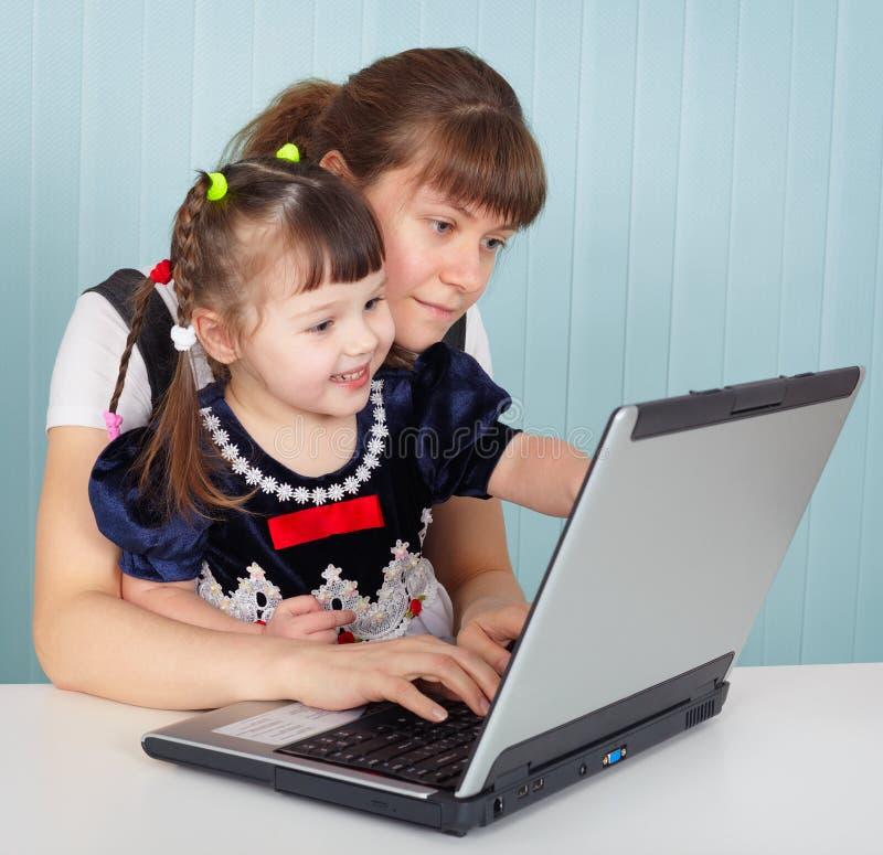 Mère et descendant jouant avec l'ordinateur portatif images libres de droits