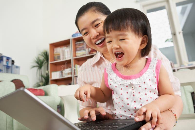 Mère et descendant jouant l'ordinateur portatif ensemble photographie stock libre de droits