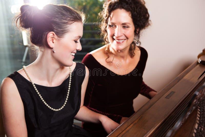 Mère et descendant jouant le piano images libres de droits