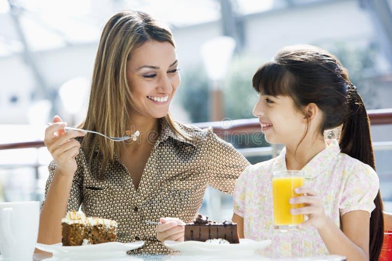 Mère et descendant mangeant le gâteau en café images libres de droits