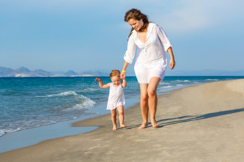 Mère et descendant marchant sur la plage image stock