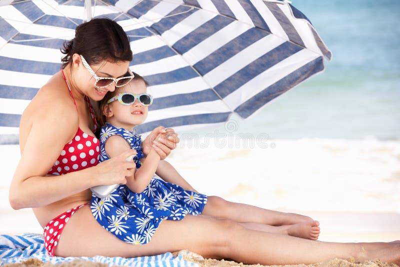 Mère et descendant mettant sur la crème de Sun images libres de droits