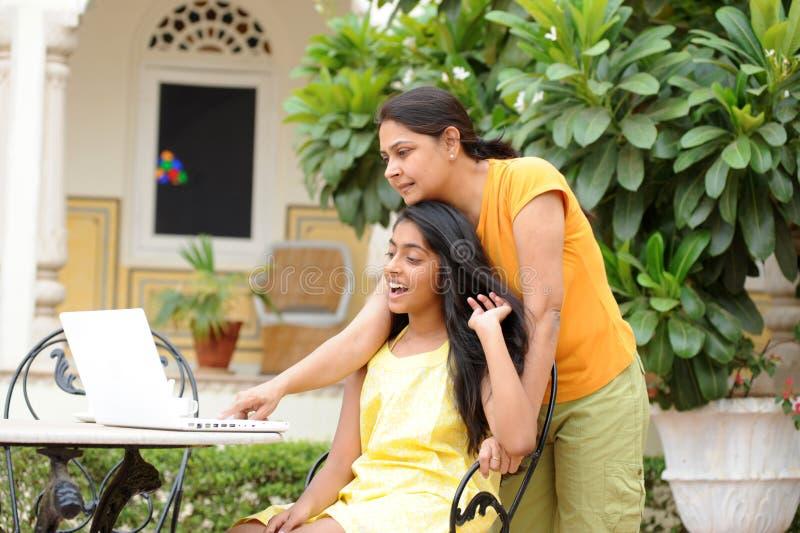 Mère et descendant partageant l'ordinateur à l'extérieur photographie stock