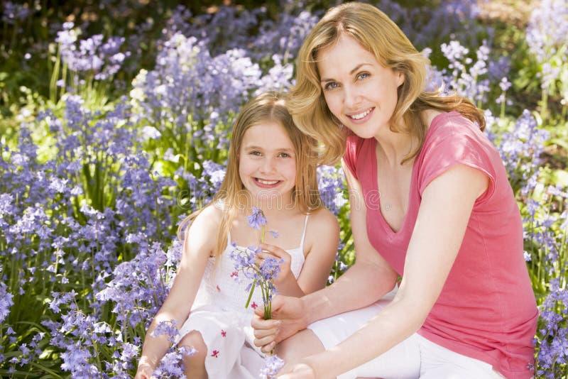 Mère et descendant retenant à l'extérieur des fleurs image libre de droits