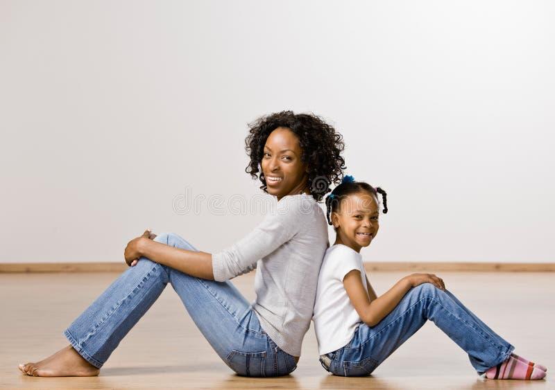 Mère et descendant s'asseyant de nouveau au dos images stock