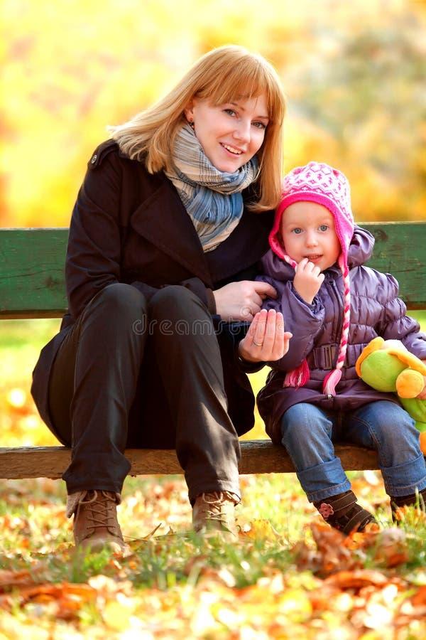 Mère et descendant s'asseyant sur un banc en stationnement photos stock