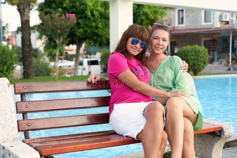 Mère et descendant s'asseyant sur un banc en stationnement images stock