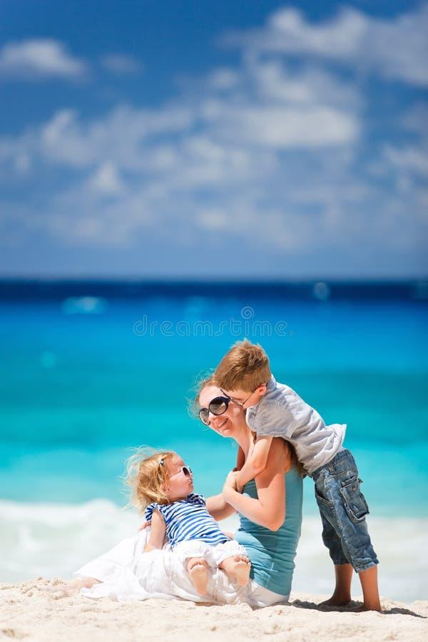Mère et deux gosses à la plage images stock