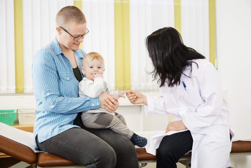 Mère et docteur With Baby Sitting sur le lit photographie stock