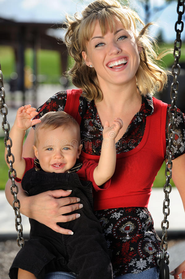Mère et enfant à l'oscillation de cour de jeu image libre de droits