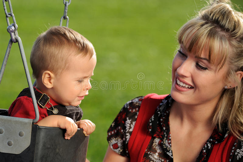 Mère et enfant à l'oscillation de cour de jeu images libres de droits