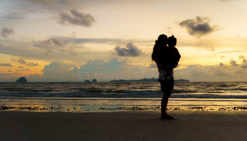 Mère et enfant à la plage de coucher du soleil image libre de droits