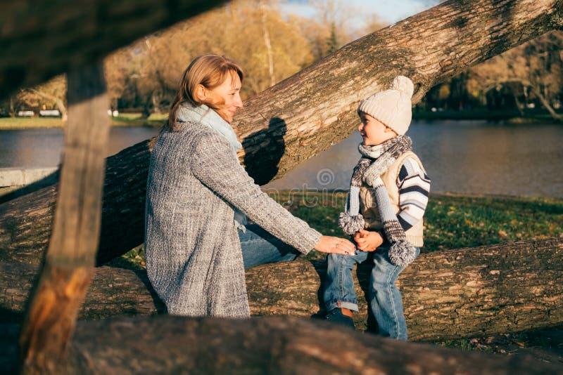 Mère et enfant étreignant au parc d'automne près du lac photos stock