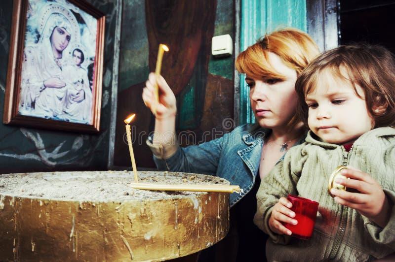 Mère et enfant allumant des bougies dans l'église photographie stock libre de droits