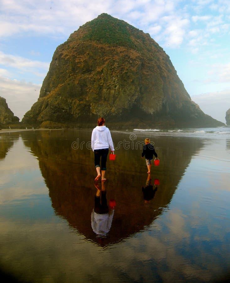 Mère et enfant avec le seau rouge sur la plage réfléchie photographie stock