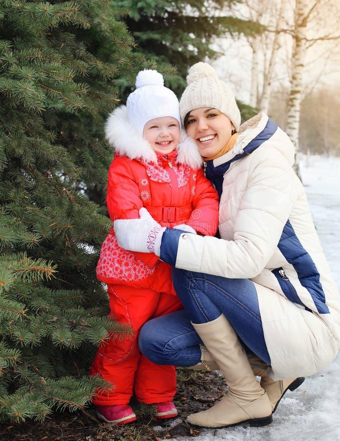 Mère et enfant de sourire heureux près d'arbre de Noël en hiver photos libres de droits