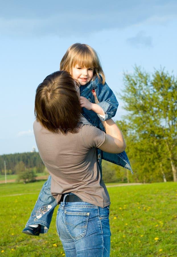 Mère et enfant jouant sur le pré photographie stock libre de droits