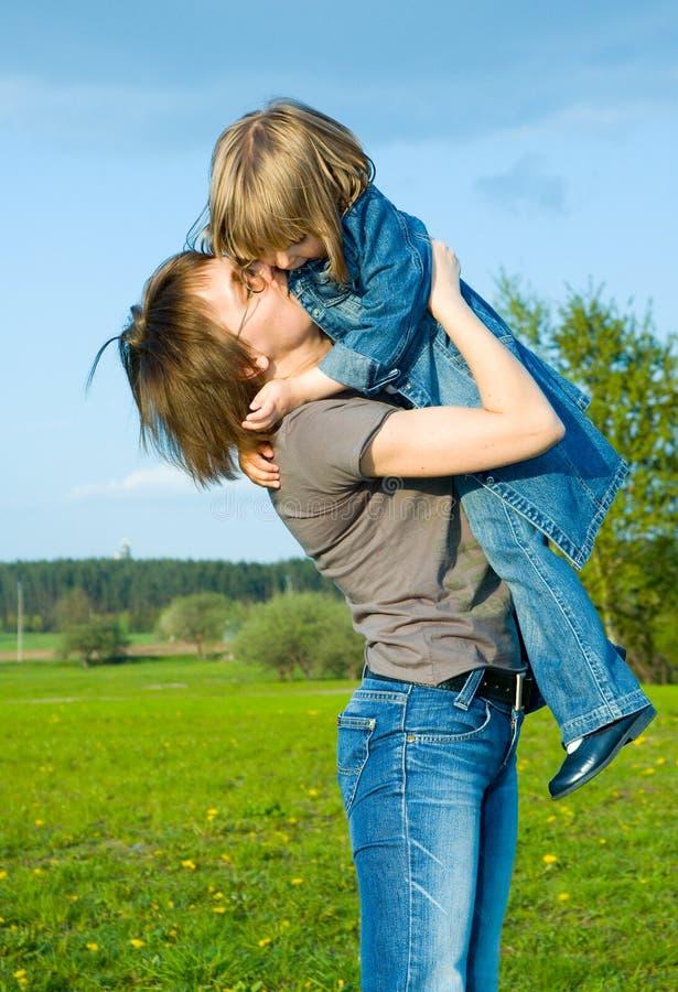 Mère et enfant jouant sur le pré photo stock