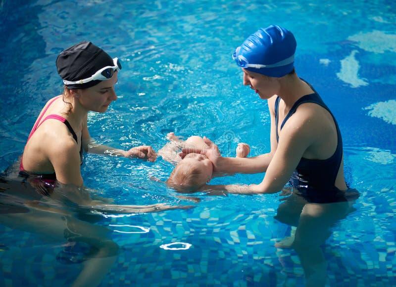 Mère et enfant nouveau-né à la classe de natation infantile Leçons de natation de mise en oeuvre d'instructeur féminin pour le pa images libres de droits