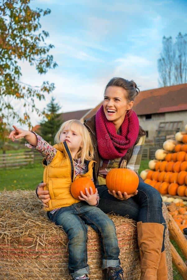 Mère et enfant s'asseyant sur la meule de foin avec des potirons image stock