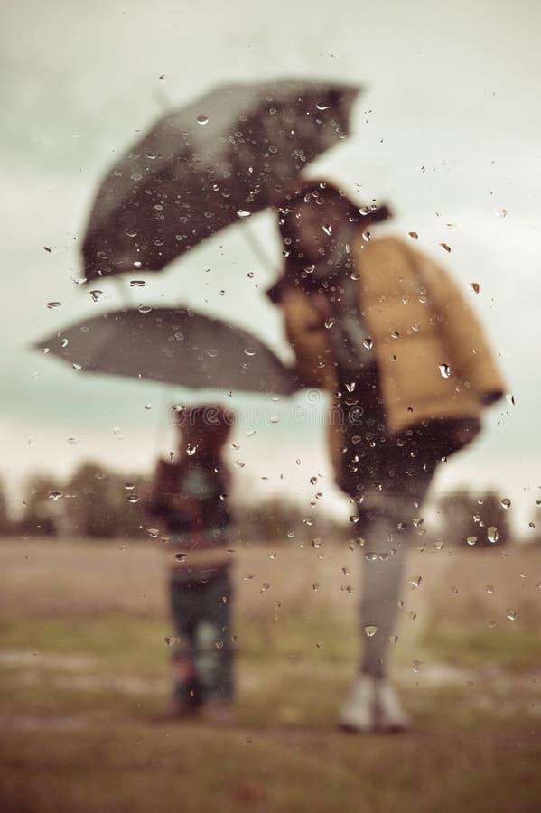 Mère et enfant sous la silhouette de parapluie par la fenêtre humide photos libres de droits