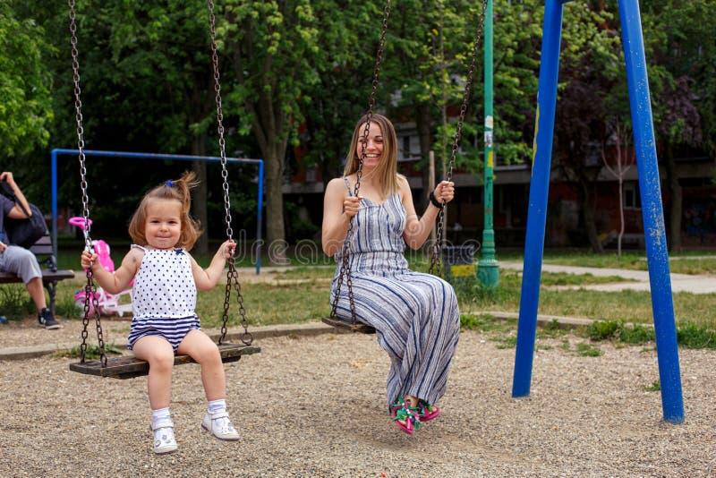 Mère et enfant sur l'oscillation au terrain de jeu photos libres de droits