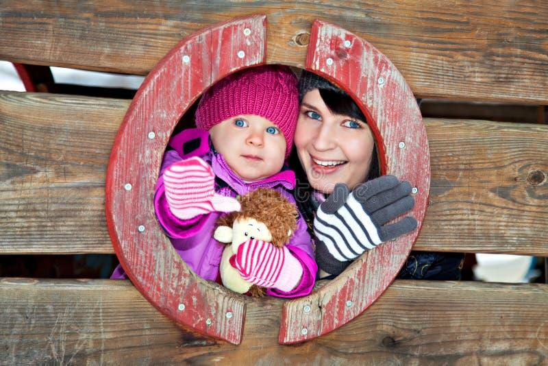 Mère et enfant sur le terrain de jeu de l'hiver image stock