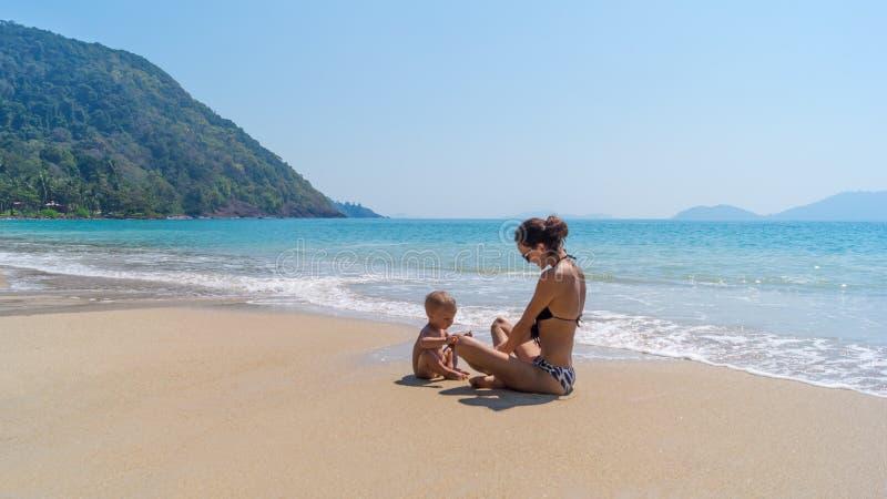 Mère et enfant sur une plage sablonneuse photographie stock libre de droits